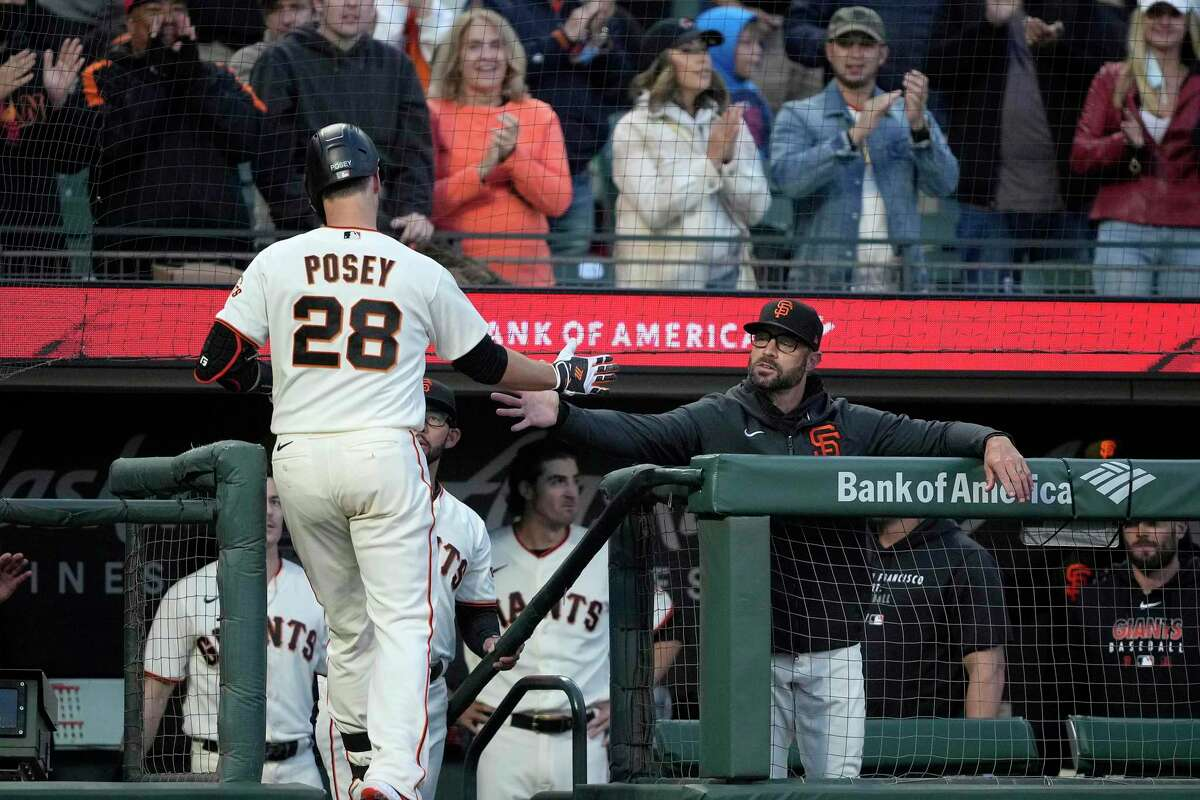 San Francisco Giants' Buster Posey (28) is congratulated by manager Gabe Kapler, right, after hitting a solo home run against the Arizona Diamondbacks during the third inning of a baseball game Wednesday, Aug. 11, 2021, in San Francisco. (AP Photo/Tony Avelar)