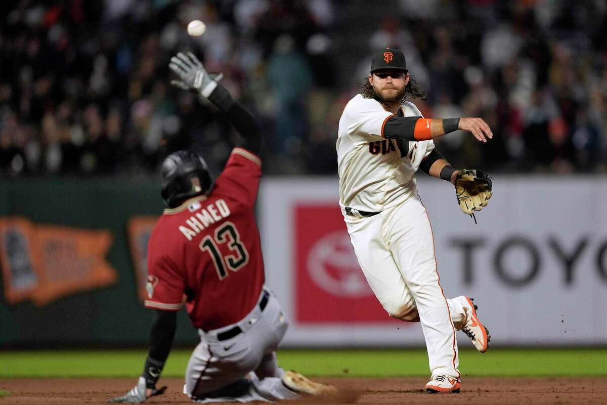San Francisco Giants shortstop Brandon Crawford throws to first base after forcing out Arizona Diamondbacks' Nick Ahmed (13) at second base during the fourth inning of a baseball game Wednesday, Aug. 11, 2021, in San Francisco. Merrill Kelly was out at first for the double play. (AP Photo/Tony Avelar)
