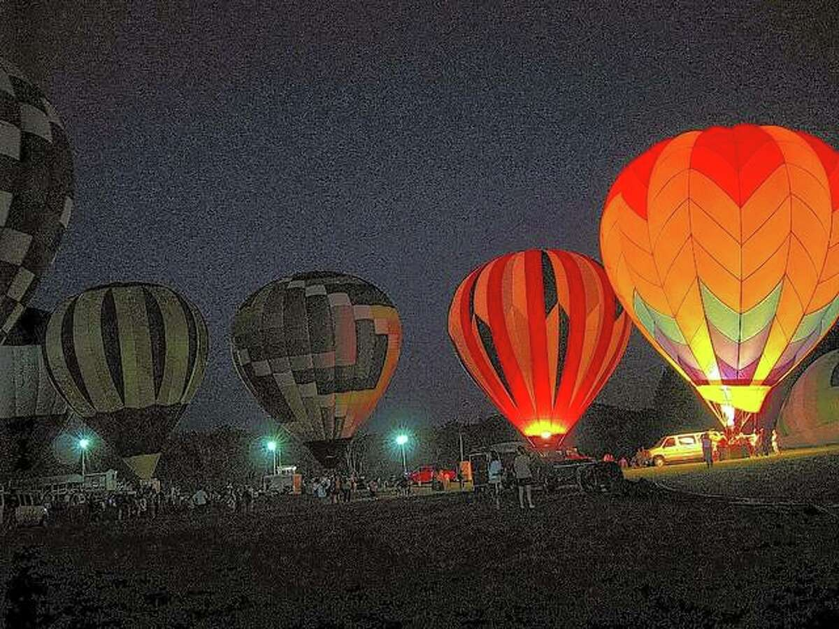 Hot-air balloons light up the night sky during a Quad Cities Balloon Festival night glow.