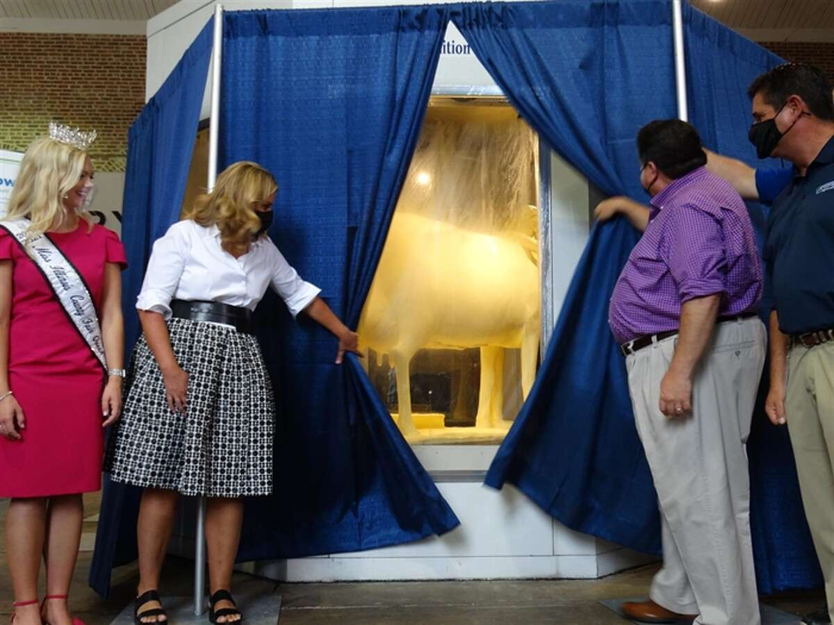 Gov. JB Pritzker and First Lady MK Pritzker unveil the Illinois State Fair's 2021 butter cow, along with Department of Agriculture Director Jerry Costello II, far right, and 2021 Miss Illinois County Fair Queen Kelsi Kessler. (Capitol News Illinois photo by Peter Hancock)