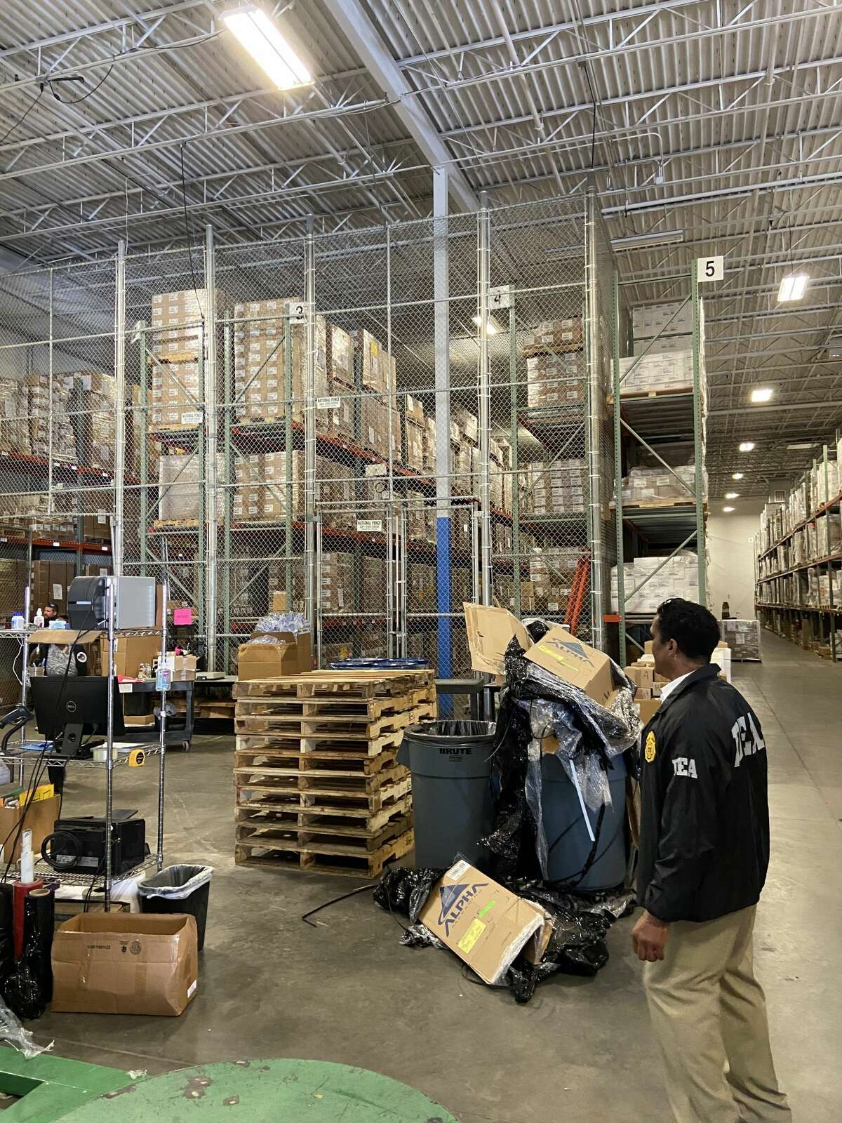 Houston DEA Associate Special Agent in Charge Antonio Hubbard looks over evidence removed from the Woodfield Distribution Center in Sugar Land during a seizure Wednesday, August 11.