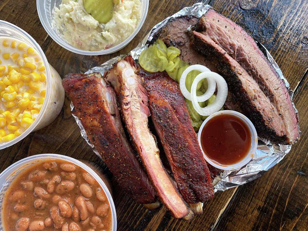 Meat and sides include, clockwise from right, sliced brisket, pork ribs, pinto beans, creamed corn and potato salad at Whiskey Tango Foxtrot BBQ, a food trailer parked beside the Stout House bar on Potranco Road near Texas 151 on San Antonio's West Side.