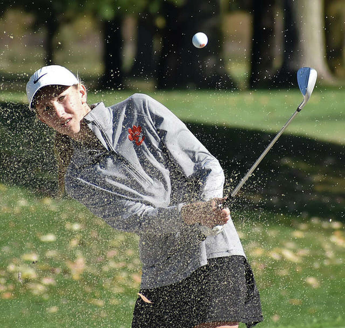 Edwardsville's Grace Daech watches her shot fly out of the bunker during a tournament last season for the Tigers.