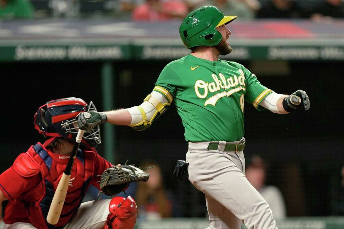 Oakland Athletics' Jed Lowrie watches his RBI double during the 10th inning of the team's baseball game against the Cleveland Indians, Tuesday, Aug. 10, 2021, in Cleveland. Oakland won 4-3 in 10 innings. (AP Photo/Tony Dejak)