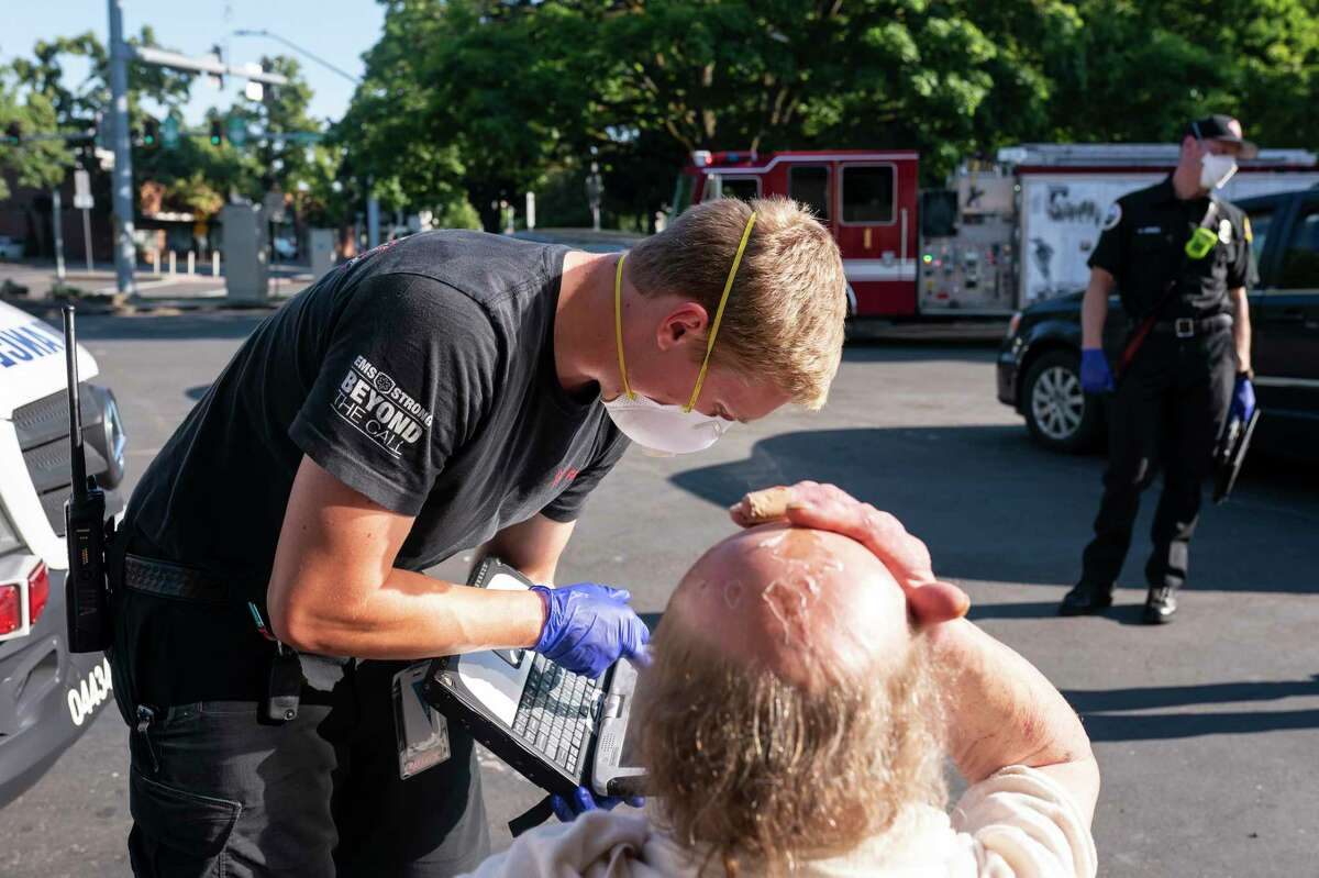 A paramedic treats a man experiencing heat exposure during June's heat wave in Oregon.