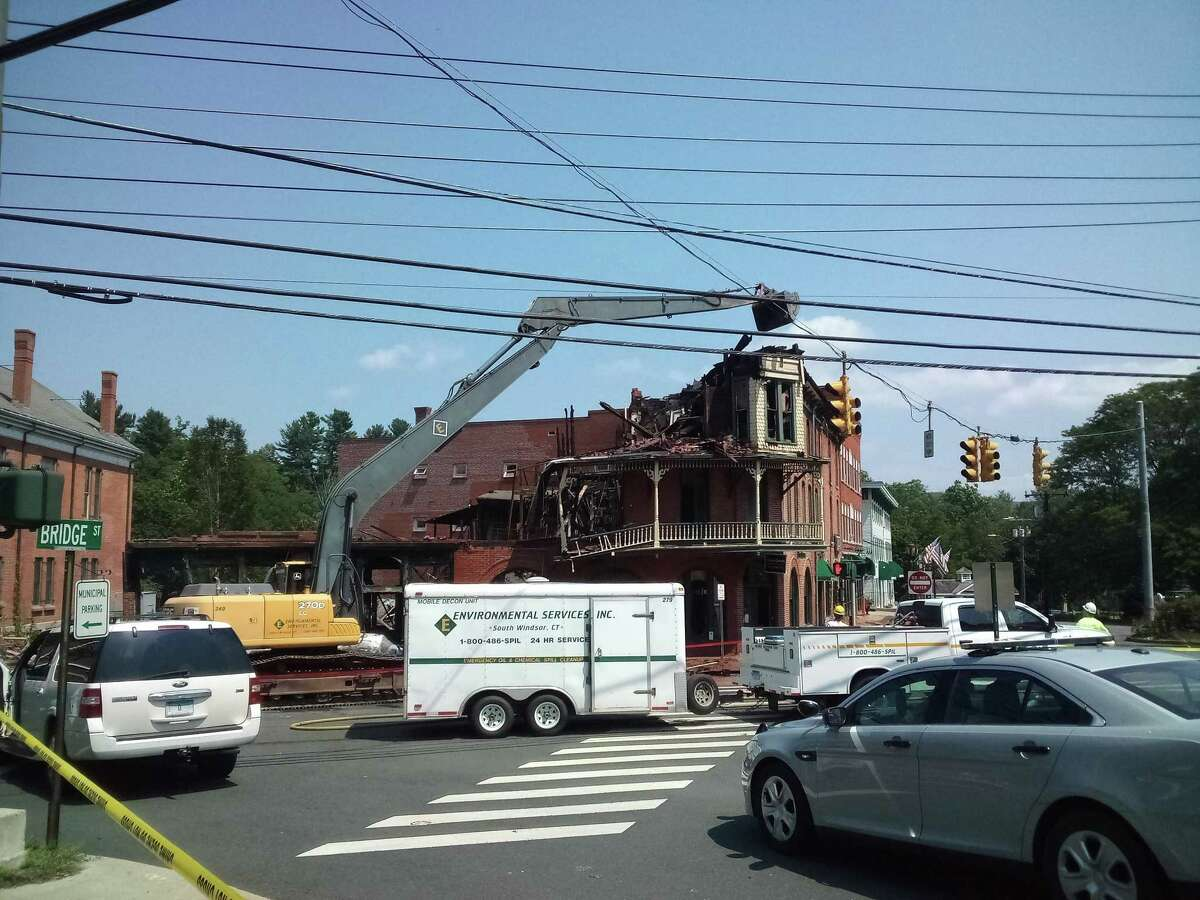 Residents watch as the New Hartford House is torn down Wednesday, after a devastating fire damaged it beyond repair a day earlier.