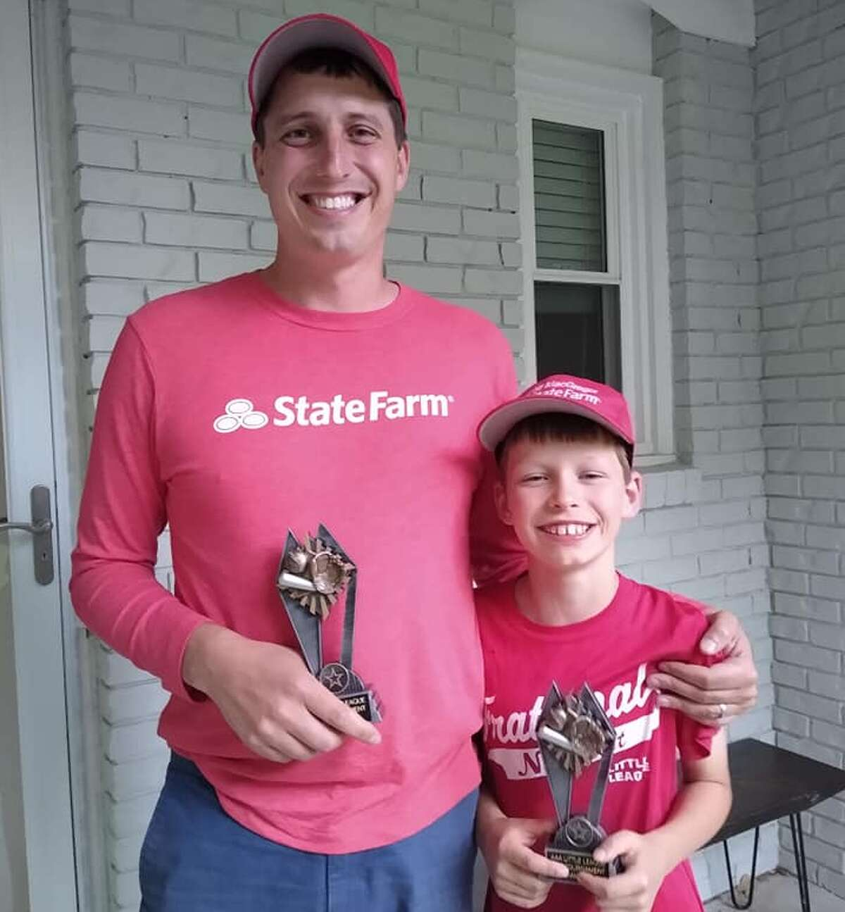 Midland's Grayson Skorup, alongside his father Jarrett, poses with his championship trophy after winning the local Pitch, Hit and Run local competition in the Boys' 7-8 baseball age division at Dow Diamond on May 15, 2021. Skorup will compete in the state finals at Comerica Park in Detroit on Aug. 28.