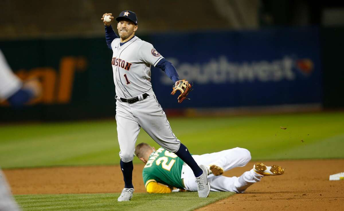 Carlos Correa of the Houston Astros turns two after colliding with Oakland's Matt Chapman during the game against the Athletics at RingCentral Coliseum on April 2, 2021 in Oakland, California.
