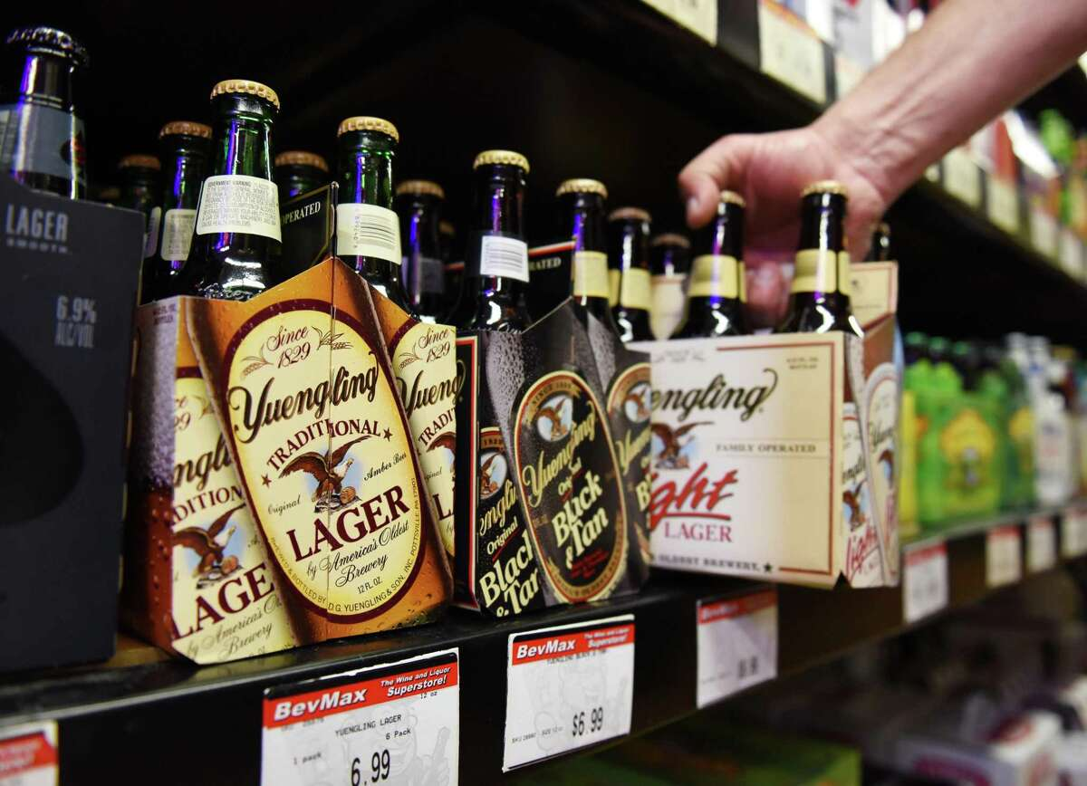 """Store Manager Keith Restivo takes a six-pack of Yuengling off the shelf at BevMax Wines & Liquors in Bridgeport, Conn. Friday, Oct. 10, 2014. Yuengling has not been available in Connecticut since 1996 but made its return to the state earlier this week and is now available at most local package stores. Pronounced """"ying-ling,"""" the beer is an amber lager brewed at America's oldest brewery in Pottsville, Pa. and comes in a low-calorie light version as well as a black-and-tan version that combines a porter with premium beer."""