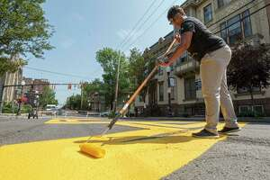 Tandra LaGrone, of In Our Own Voices, re-paints the Black Lives Matter mural on Thursday, Aug. 12, 2021 in Albany, N.Y. Lark St. between Lancaster St. to Hudson Ave. is closed to traffic until the painting is completed and dried. City of Albany workers also helped paint.