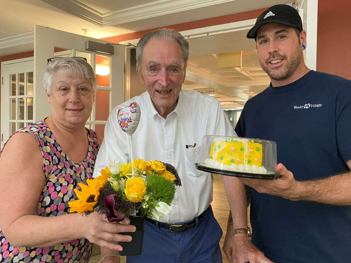Longtime Wesley Village senior living campus in Shelton residents Ken, and Doris Steeves, recently celebrated their 70th wedding anniversary on Tuesday, July 14. Crosby Commons team members Cathy Brelsford, (left), and Jim Tomchik, (right), pose with Ken, (middle), before a visit to see his wife Doris on their 70th wedding anniversary.