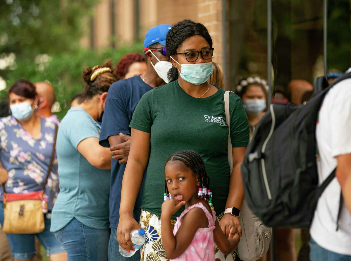 Evena Desir and her daughter, Daenelys, 5, wait in line during an enrollment drive, Tuesday, Aug. 3, 2021, at IBEW Local 716 building in Houston. Hundreds of people lined up outside and were seated inside to receive assistance signing up for the Harris County Recovery Assistance and the Houston-Harris County Emergency Rental Assistance programs.