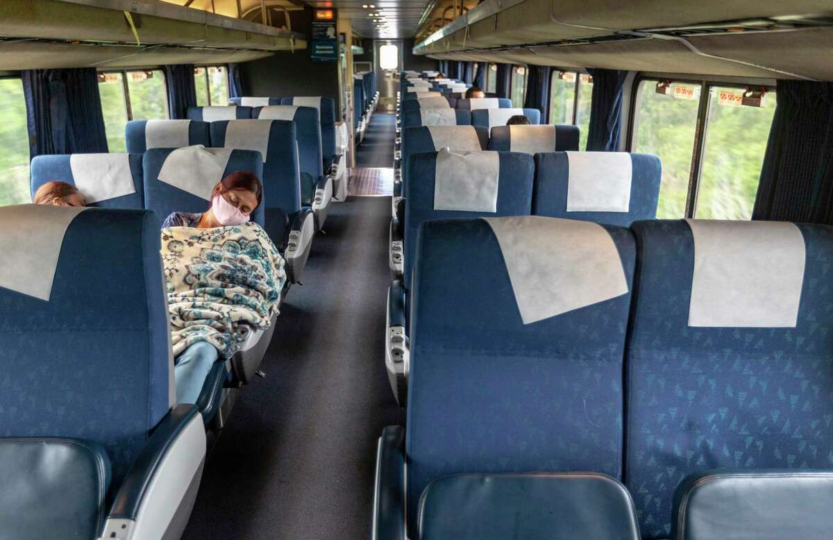 A passenger on Amtrak's Texas Eagle, which runs from San Antonio to Chicago, sleeps Monday, Aug. 9, 2021 as the train runs between San Antonio and Austin. If President Biden's infrastructure deal passes the train's current once-per-day schedule could potentially be expanded to three times per day on the San Antonio to Fort Worth section of the route.
