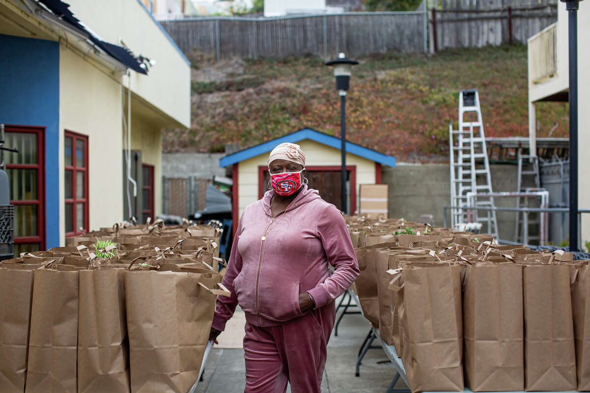 Felisia Thibodeaux, executive director of the Southwest Community Corporation,stands with bags of food she delivers to the needy from the I.T. Bookman Community Center in San Francisco on Aug. 11, 2021.