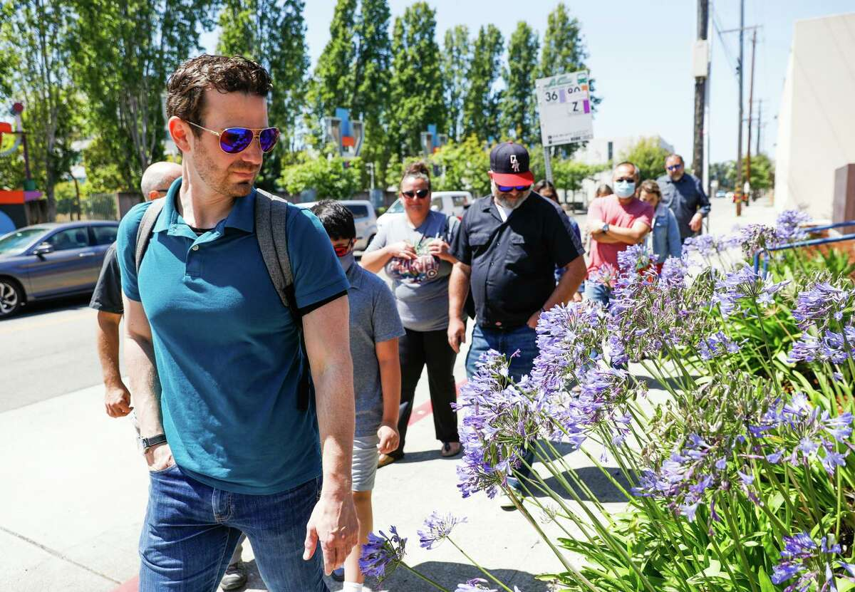 Marc Pasquinelli of San Francisco, who is colorblind, checks out flowers while wearing sunglasses with patented lenses made by EnChroma during a media tour in Berkeley.
