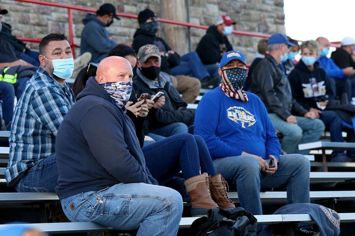 Fans sit in the stands wearing masks during the game between the Ida Bluestreaks and the Clinton Redskins on September 18, 2020 in Clinton, Michigan. (Photo by Justin Casterline/Getty Images)