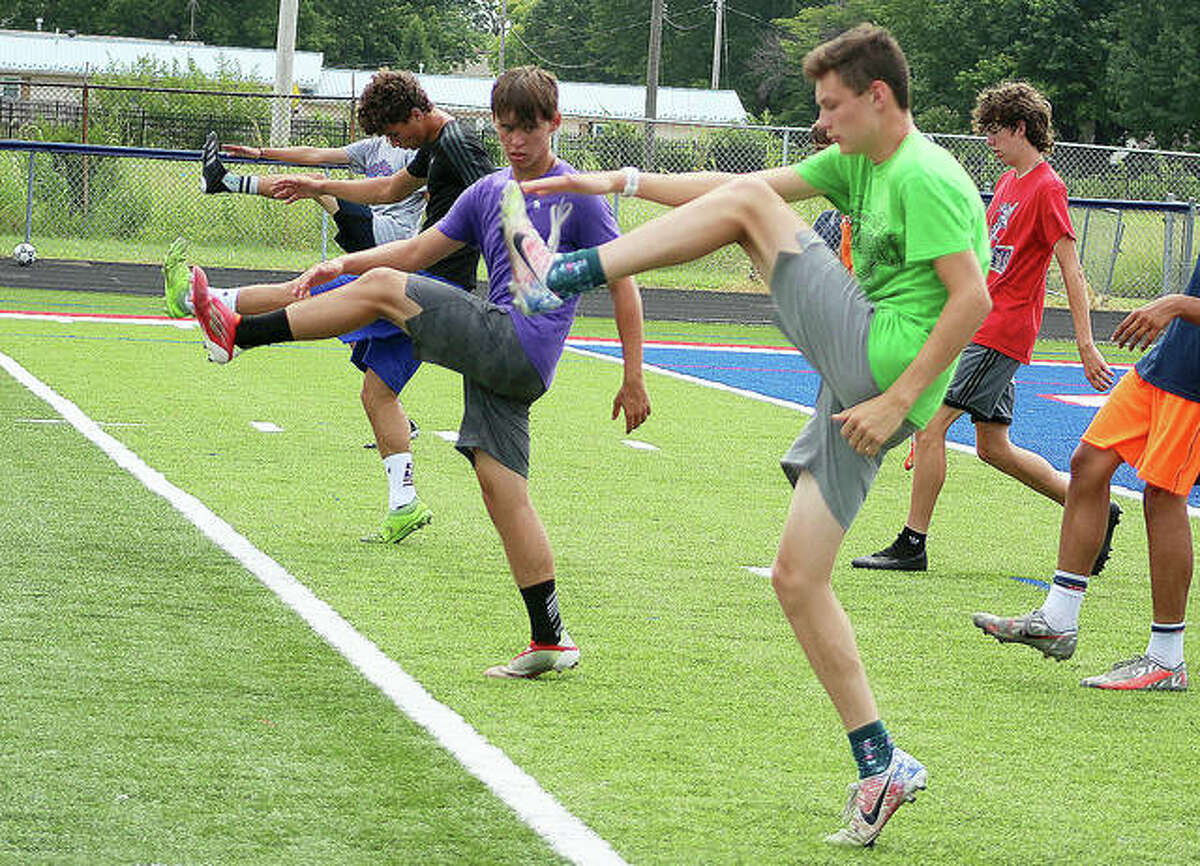 Carlinville senior Levi Yudinsky, in green, and junior teammate and the rest of the Cavaliers soccer team go through a high kick warmup drill Thursday during preseason soccer practice at Carlinville High School.