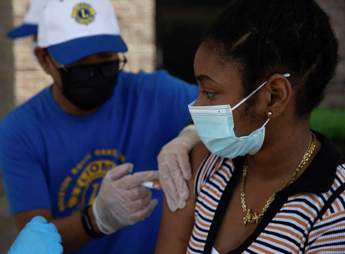 """Aniubys Alarcon, 13, receives three vaccination shots Saturday, Aug. 7, 2021, at Bush Elementary in Houston. The City of Houston held its first """"Super Saturday"""" vaccine drives, setting up free vaccination sites at 10 schools in the area in preparation for the 2021-2022 school year. Both non-COVID and COVID vaccines were available for eligible students."""
