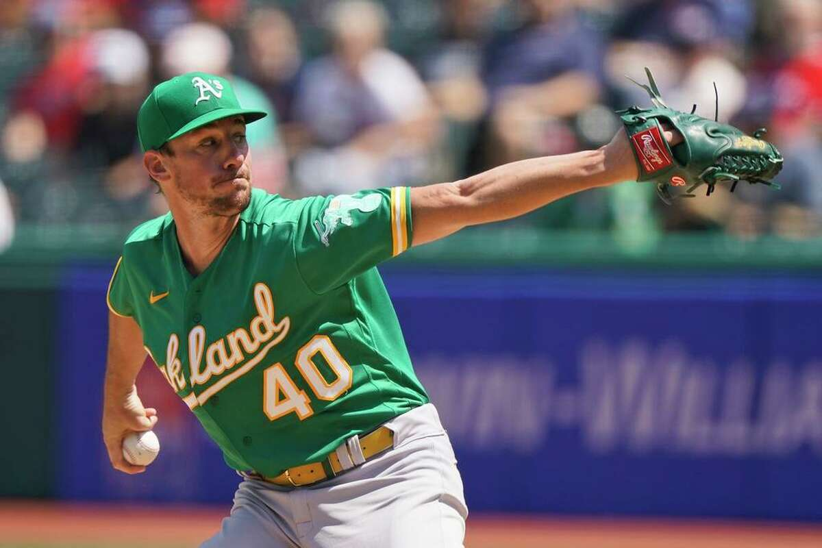 Oakland Athletics starting pitcher Chris Bassitt delivers in the first inning of a baseball game against the Oakland Athletics, Thursday, Aug. 12, 2021, in Cleveland. (AP Photo/Tony Dejak)