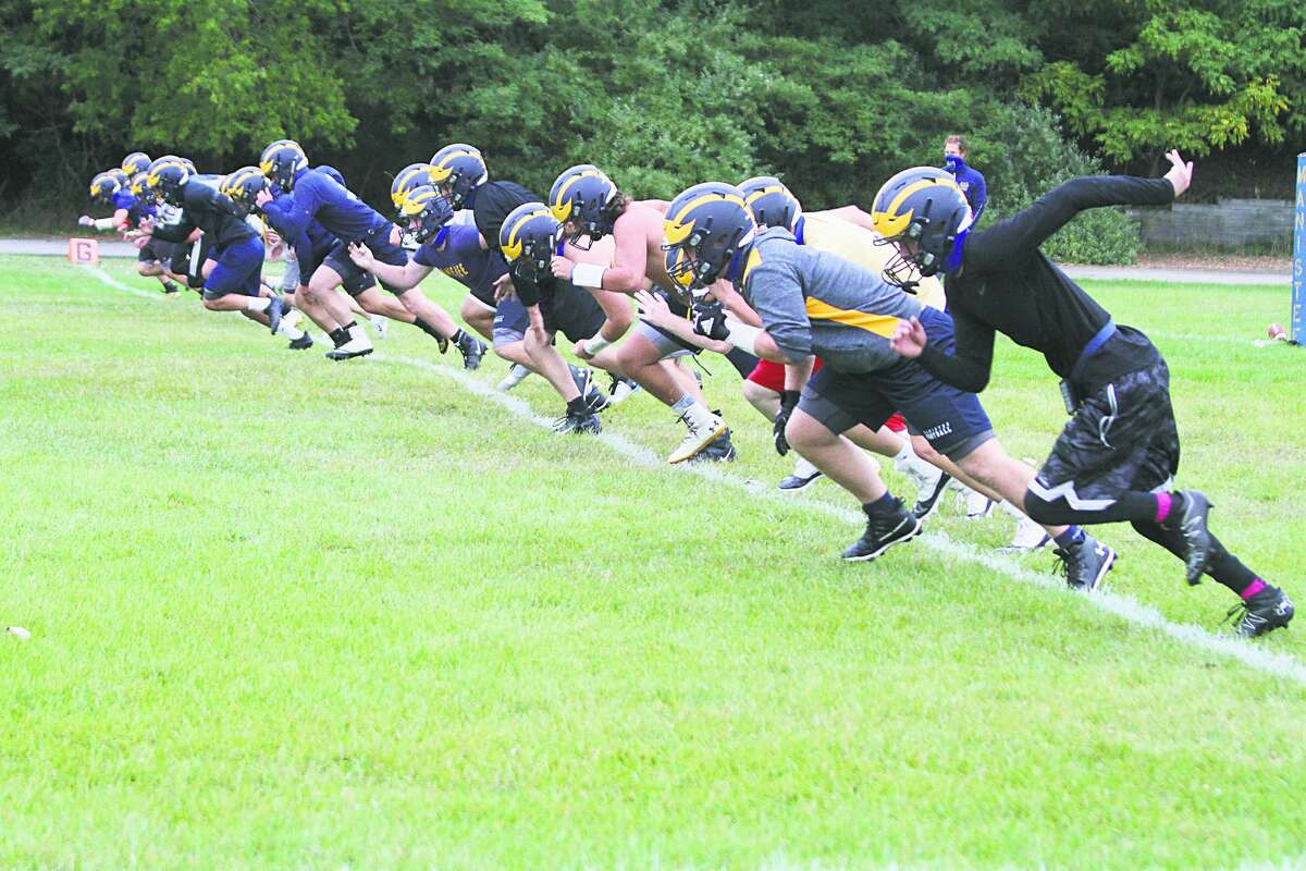 The Manistee football team runs drills on the first day of practice after the Michigan High School Athletic Association reinstated the sport for a fall season.