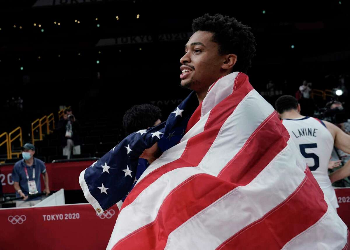 United States' Keldon Johnson drapes himself with a United States flag as he celebrates with teammates after their win over France in a men's basketball Gold medal game at the 2020 Summer Olympics, Saturday, Aug. 7, 2021, in Saitama, Japan. (AP Photo/Eric Gay)