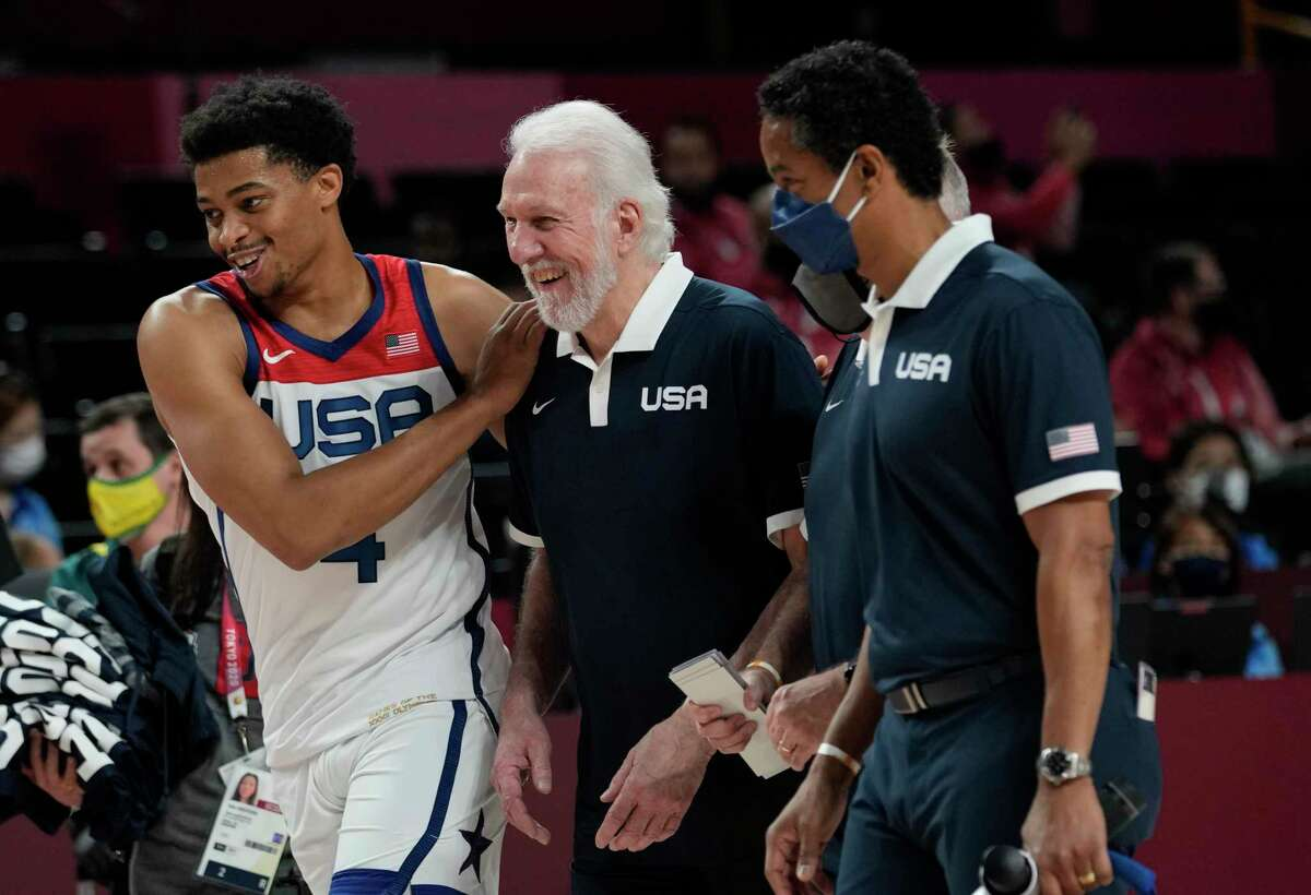 United States's Keldon Johnson (4), left, and head coach Gregg Popovich, center, celebrate after their win in the men's basketball semifinal game against Australia at the 2020 Summer Olympics, Thursday, Aug. 5, 2021, in Saitama, Japan. (AP Photo/Eric Gay)
