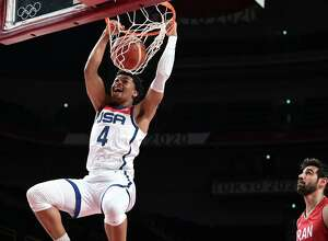 USA's Keldon Johnson (left) dunks the ball in the men's preliminary round group A basketball match between Iran and USA during the Tokyo 2020 Olympic Games at the Saitama Super Arena in Saitama on July 28, 2021. (Aris Messinis/AFP via Getty Images/TNS)