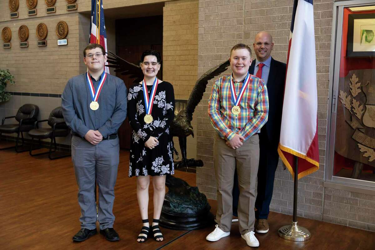 """From left to right, Dennis Hom, Peyton Tabor, Joseph """"Tres"""" Salas and Oak Ridge High School Principal AJ LiVecchi, pose for a portrait at Oak Ridge High School, Tuesday, Aug. 10, 2021, in Conroe. The students were recognized for winning during this year's UIL tournament in music."""