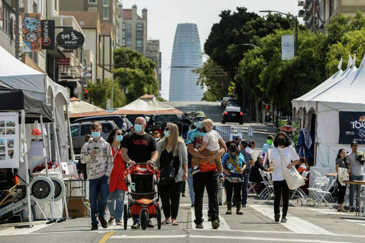 Attendees move through the annual Nihonmachi Street Fair in S.F. on Sunday. Experts say that the density of the city's population could be a factor in the increasing COVID case rate.