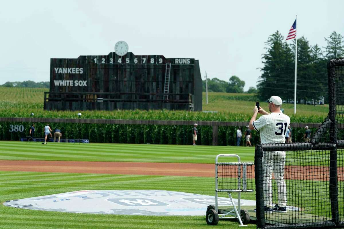 Chicago White Sox relief pitcher Liam Hendriks takes a photo on the field before a baseball game against the New York Yankees, Thursday, Aug. 12, 2021, in Dyersville, Iowa. The Yankees and White Sox are playing at a temporary stadium in the middle of a cornfield at the Field of Dreams movie site, the first Major League Baseball game held in Iowa. (AP Photo/Charlie Neibergall)