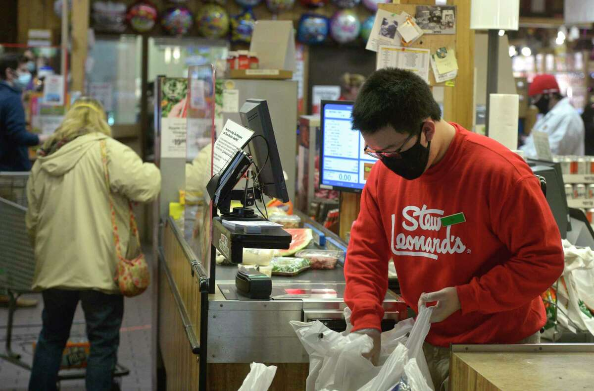 Employee Eli Taylor, of New Milford, wears a mask while working at Stew Leonard's in Danbury, Conn. Tuesday, April 21, 2020. Danbury issued a mask mandate on Wednesday, and other towns are considering following suit.