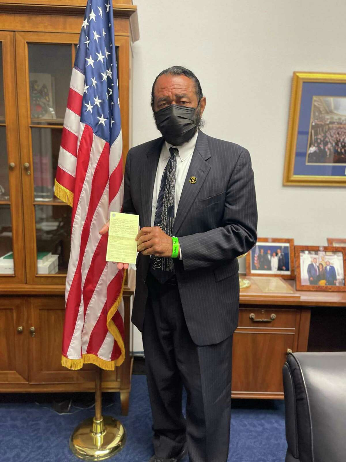 U.S. Rep. Al Green, D-Texas, holds up the citation he received after being arrested for civil disobedience while protesting voter suppression.