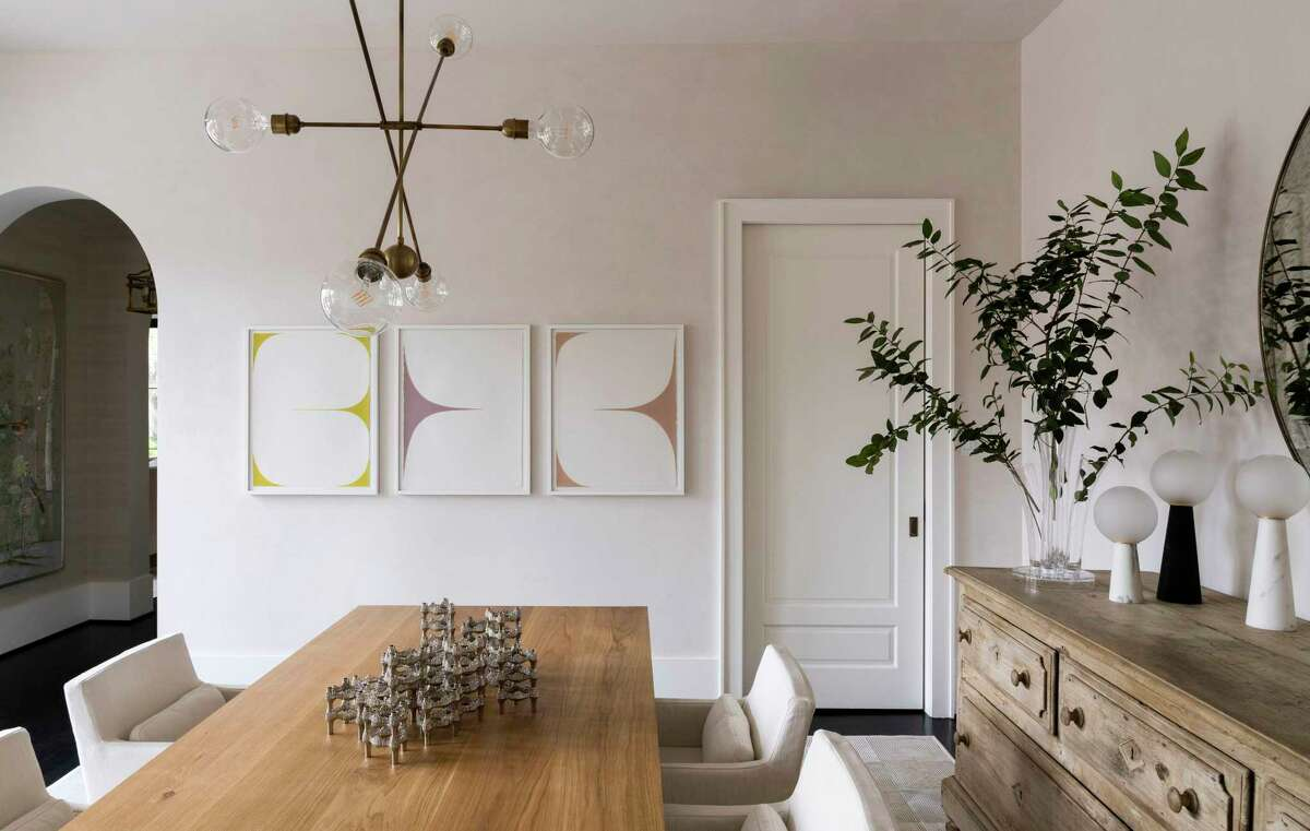 A satellite-style chandelier and Sara Genn art help decorate the dining room.