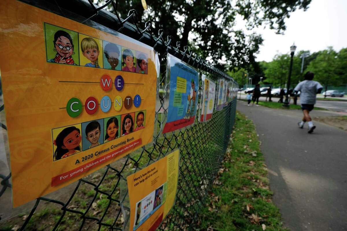 A jogger passes a 2020 Census display on a fence outside the playground at Scalzi Park on Sept. 15, 2020 in Stamford, Conn. The Census report takes place every ten years, counting those living in the United States and in its terrtories: Puerto Rico, American Samoa, the Commonwealth of the Northern Marina Islands, Guam, an the U.S. Virgin Islands.