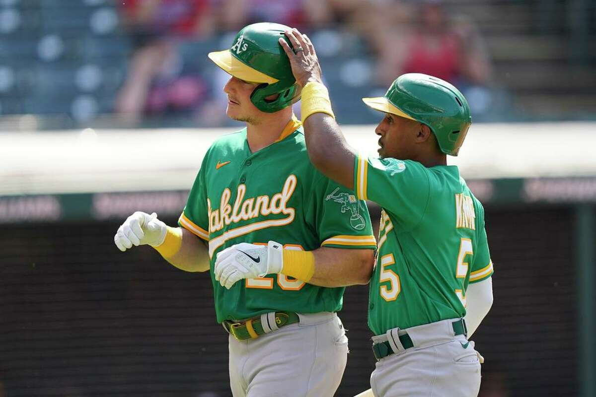 Oakland Athletics' Matt Chapman, left, and Tony Kemp celebrate after both score in the eighth inning of a baseball game against the Cleveland Indians, Thursday, Aug. 12, 2021, in Cleveland. (AP Photo/Tony Dejak)