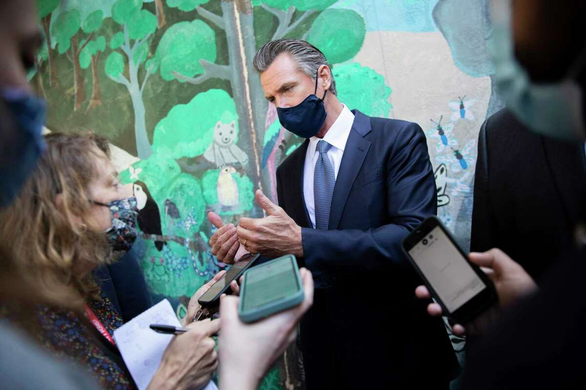 California Gov. Gavin Newsom speaks with reporters at an elementary school in Oakland on Wednesday while announcing a vaccination mandate for school teachers and staff, as the state battles the delta variant.