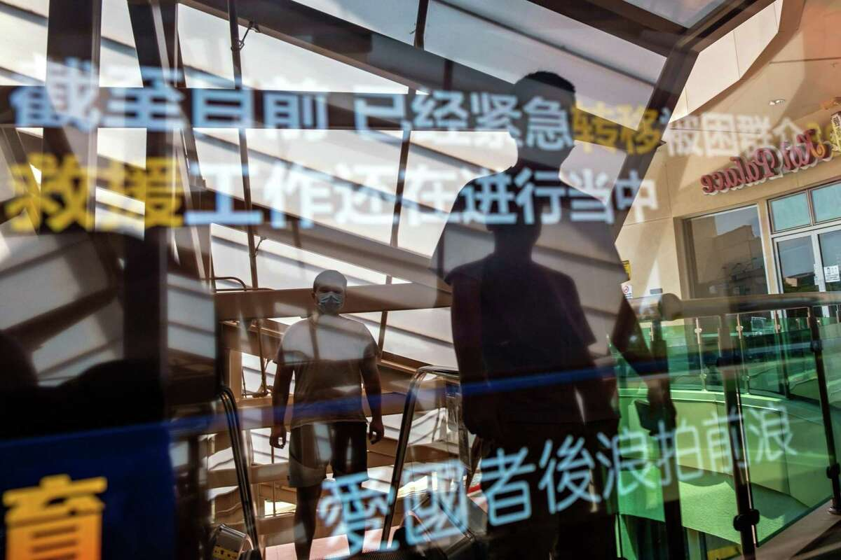 People are reflected in a video screen displaying advertisements in Chinese at a mall in Dublin, which is the fastest-growing Bay Area city, with an Asian American population driving the increase.