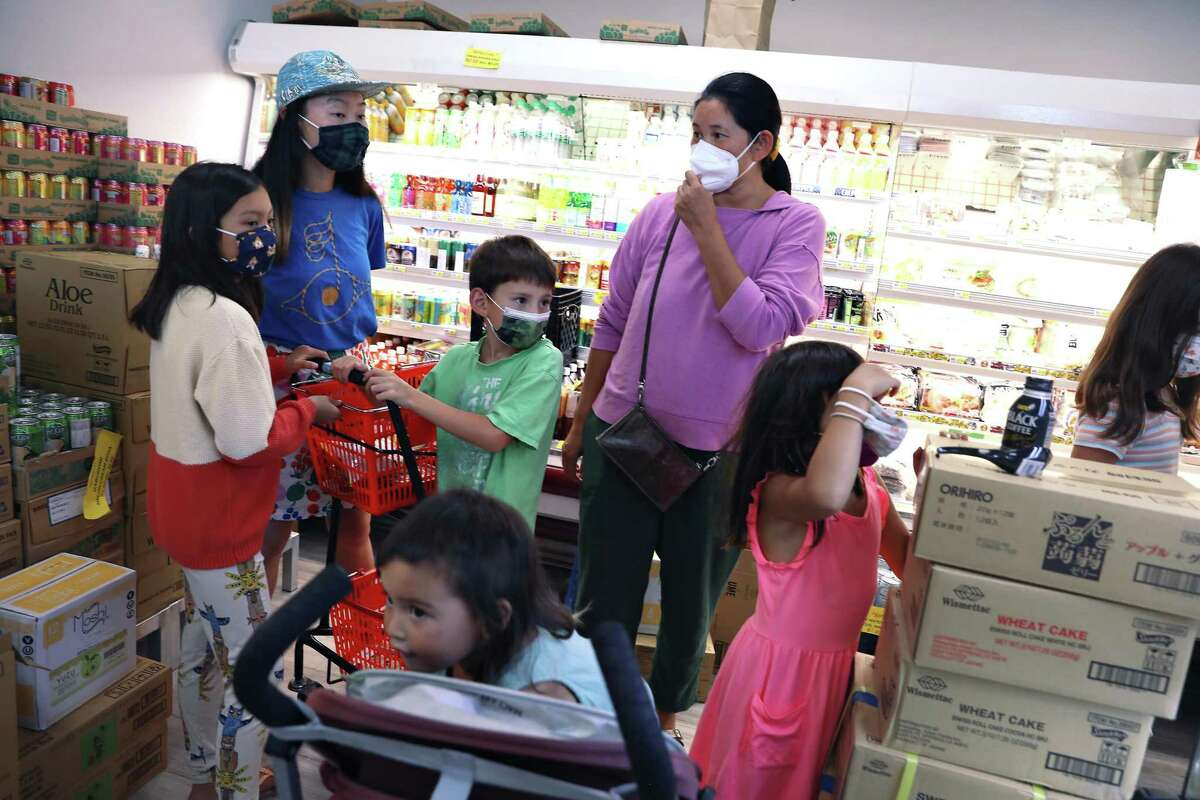 Keiko McClure (rear left) and Asel Ibragimova (rear right) shop with their children at Suruki Supermarket in San Mateo.