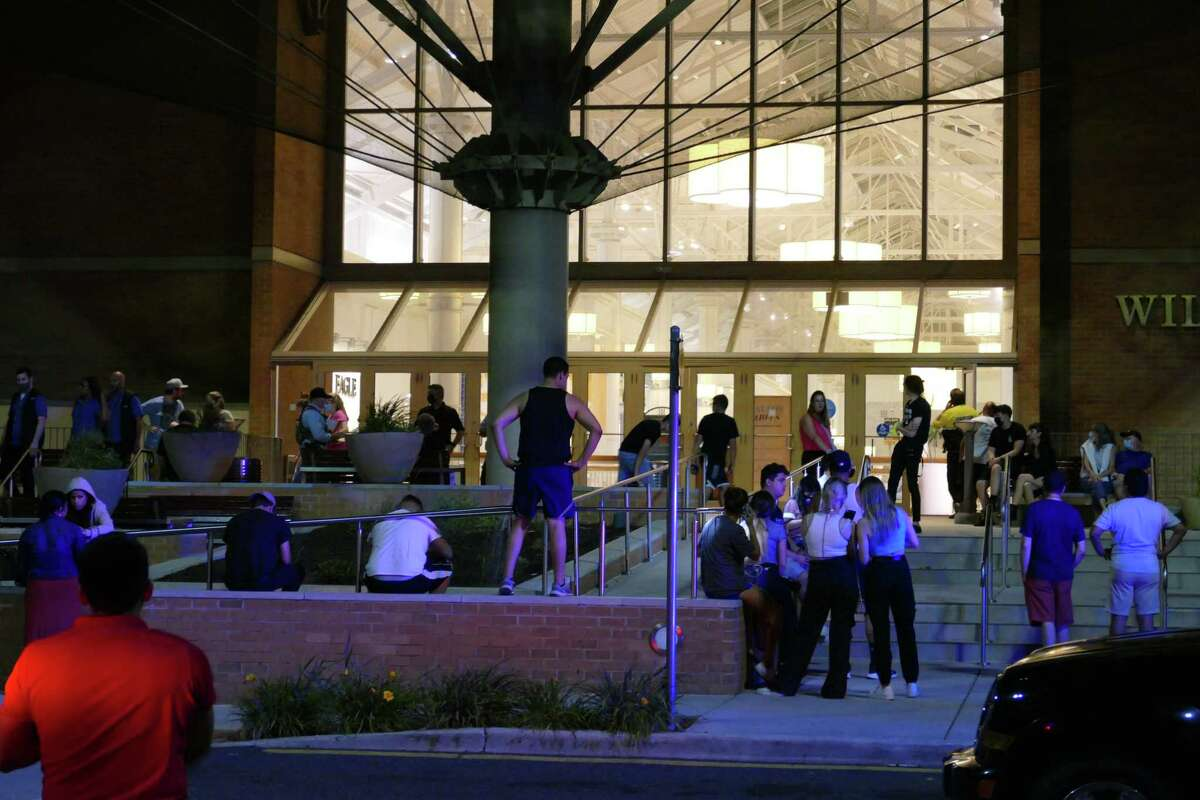 People wait outside the Danbury Fair Mall in Danbury, Conn. on Wednesday, Aug. 11, 2021 after the non-fatal shooting of a 16-year-old girl locked the mall down.
