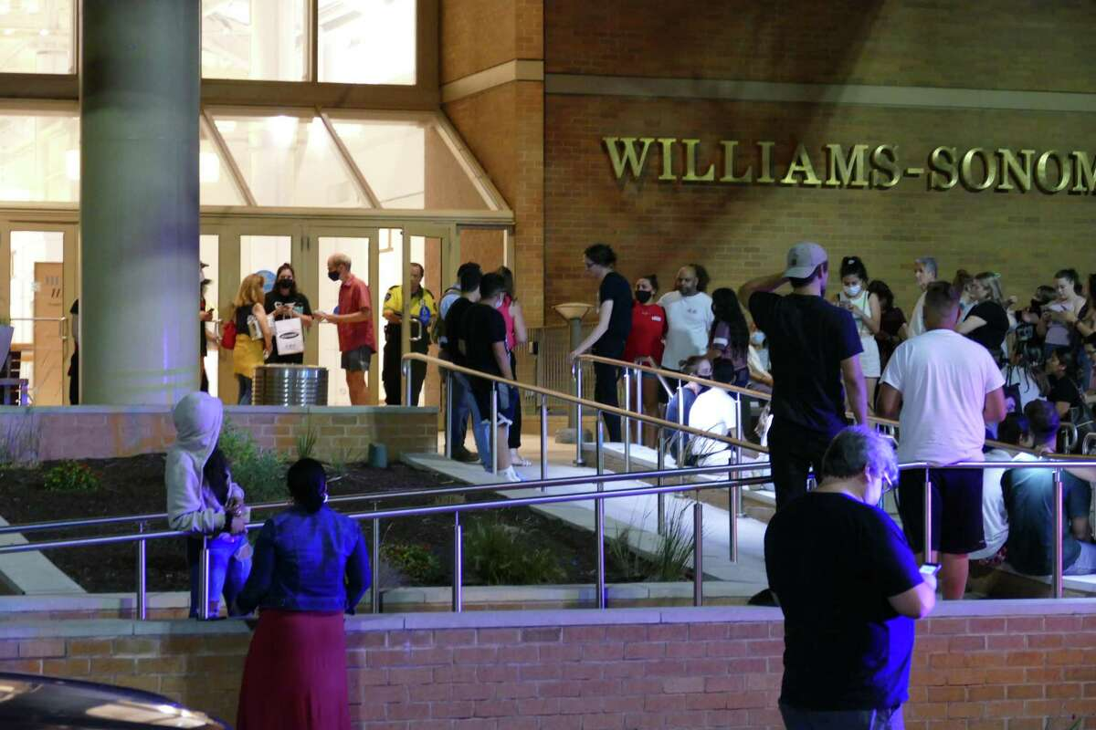 People wait outside the Danbury Fair Mall in Danbury, Conn. on Wednesday, Aug. 11, 2021 after the non-fatal shooting of a 15-year-old girl locked the mall down.