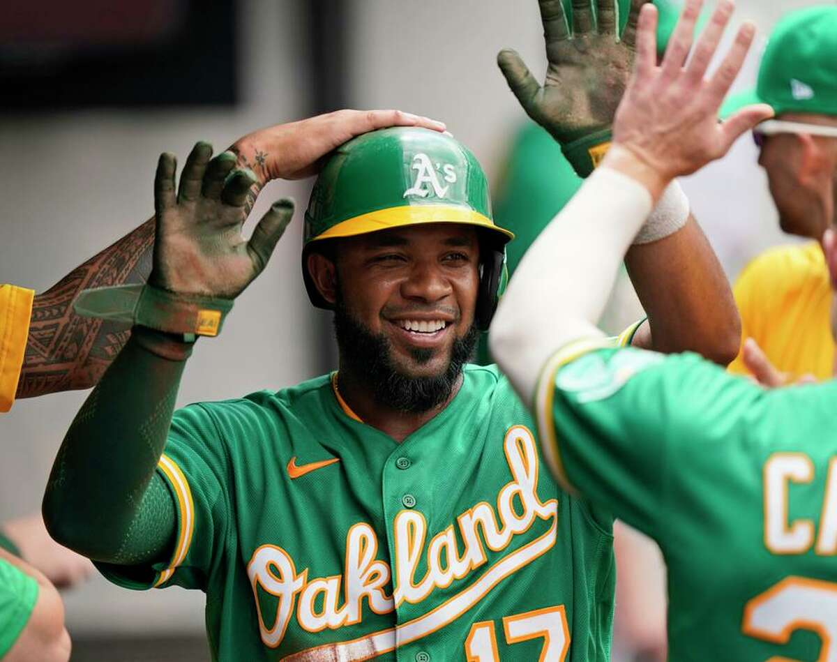 Oakland Athletics' Elvis Andrus is congratulated by teammates after scoring in the fourth inning of a baseball game against the Cleveland Indians, Thursday, Aug. 12, 2021, in Cleveland. (AP Photo/Tony Dejak)