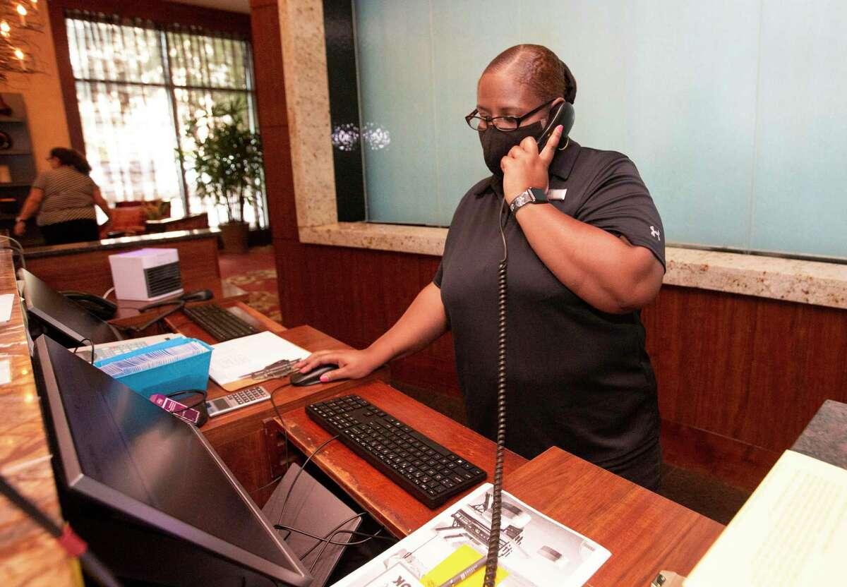 Embassy Suites front desk agent Nicole Hatchet helping a guest on the phone Thursday, Aug. 12, 2021, in Houston. The hotel had a block of rooms reserved for Offshore Technology Conferenc, which will kick off this weekend, but few of the rooms have actually been purchased.