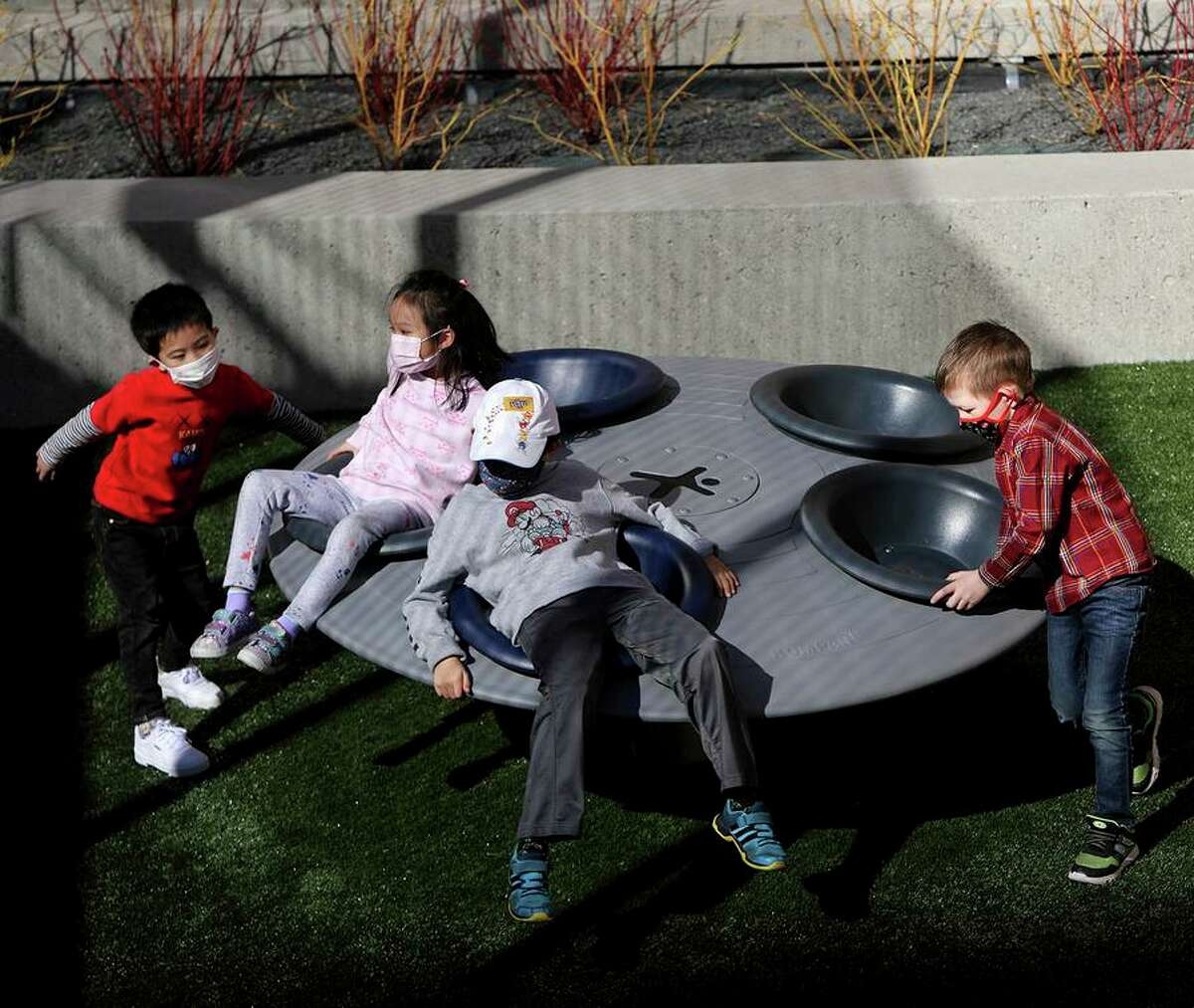"""Children play on a merry-go-round at the Willie """"Woo Woo"""" Wong Playground in Chinatown in January."""