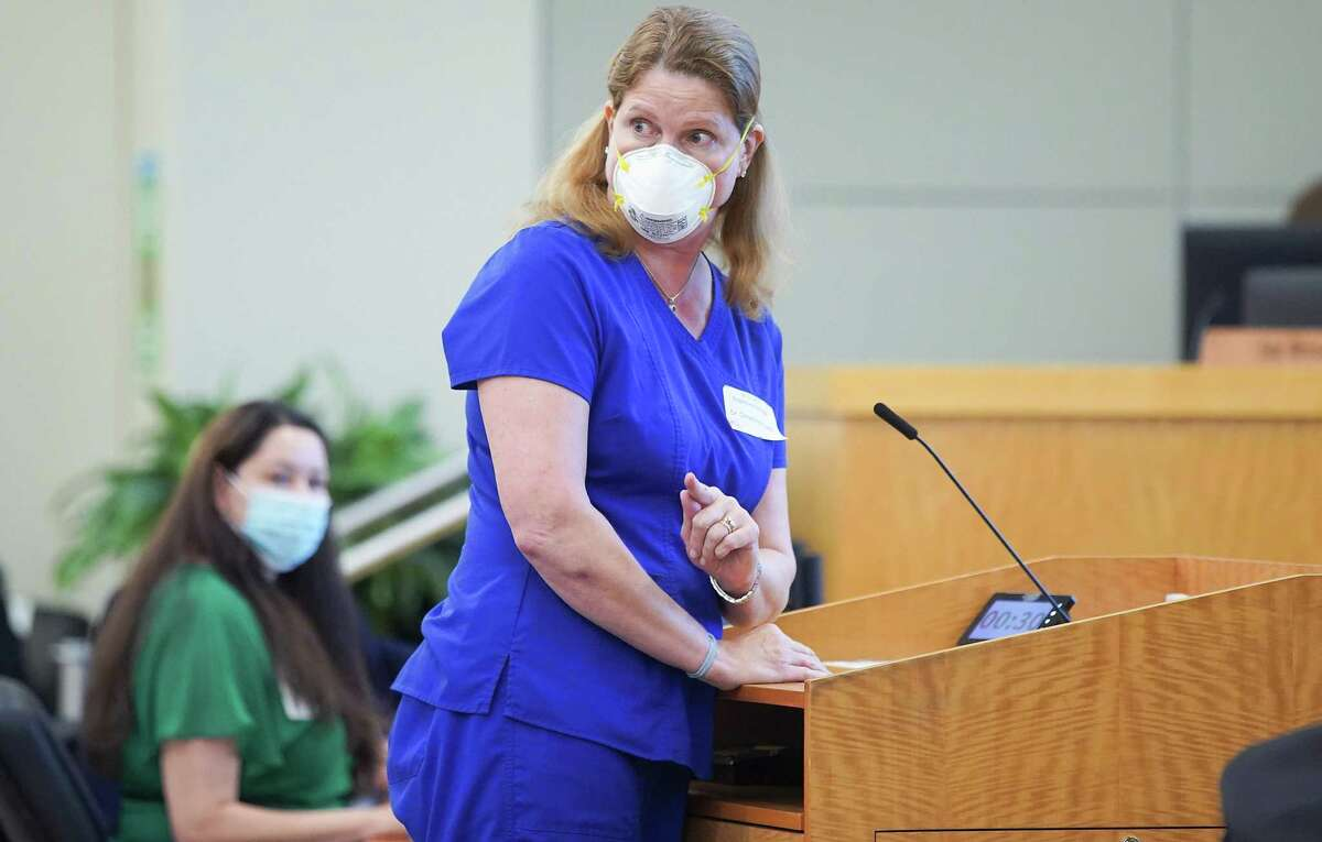 Pediatrician Christina Propst pushes back as the crowd interrupts her while she talks in favor of a mask mandate Thursday at the HISD board's meeing.