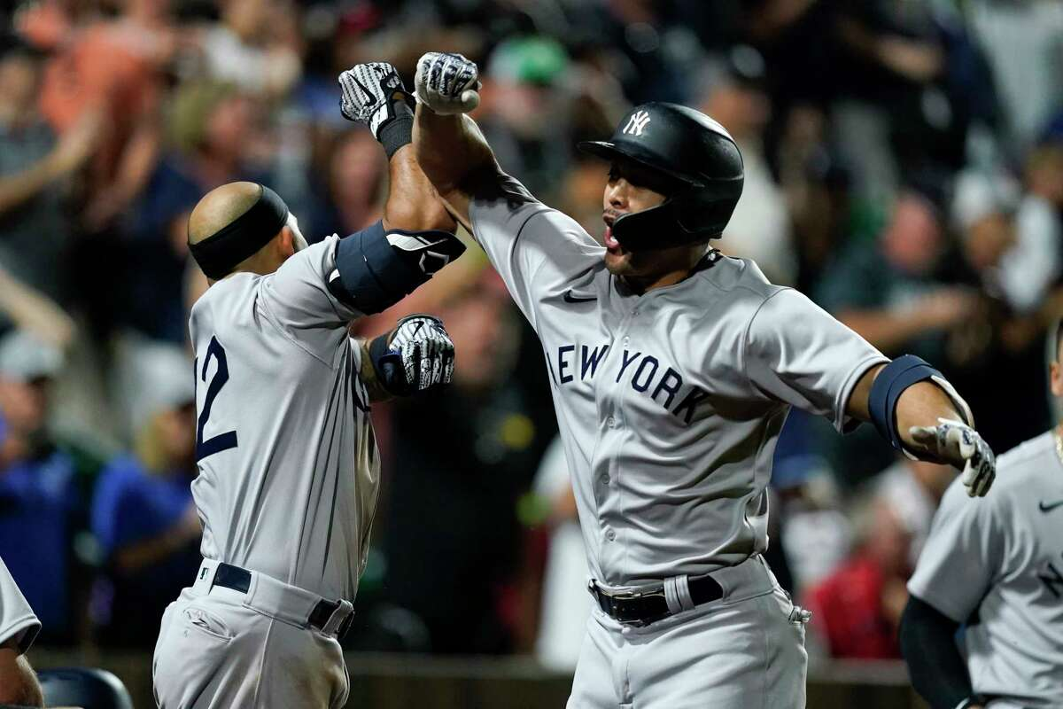 New York Yankees' Giancarlo Stanton celebrates with Rougned Odor (12) after hitting a two-run home run against the Chicago White Sox in the ninth inning during a baseball game, Thursday, Aug. 12, 2021 in Dyersville, Iowa. The Yankees and White Sox are playing at a temporary stadium in the middle of a cornfield at the Field of Dreams movie site, the first Major League Baseball game held in Iowa. (AP Photo/Charlie Neibergall)
