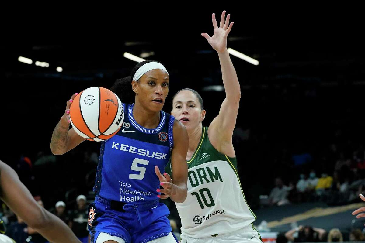 Connecticut Sun guard Jasmine Thomas (5) drives as Seattle Storm guard Sue Bird (10) defends during the second half of the Commissioner's Cup WNBA basketball game, Thursday, Aug. 12, 2021, in Phoenix. (AP Photo/Matt York)