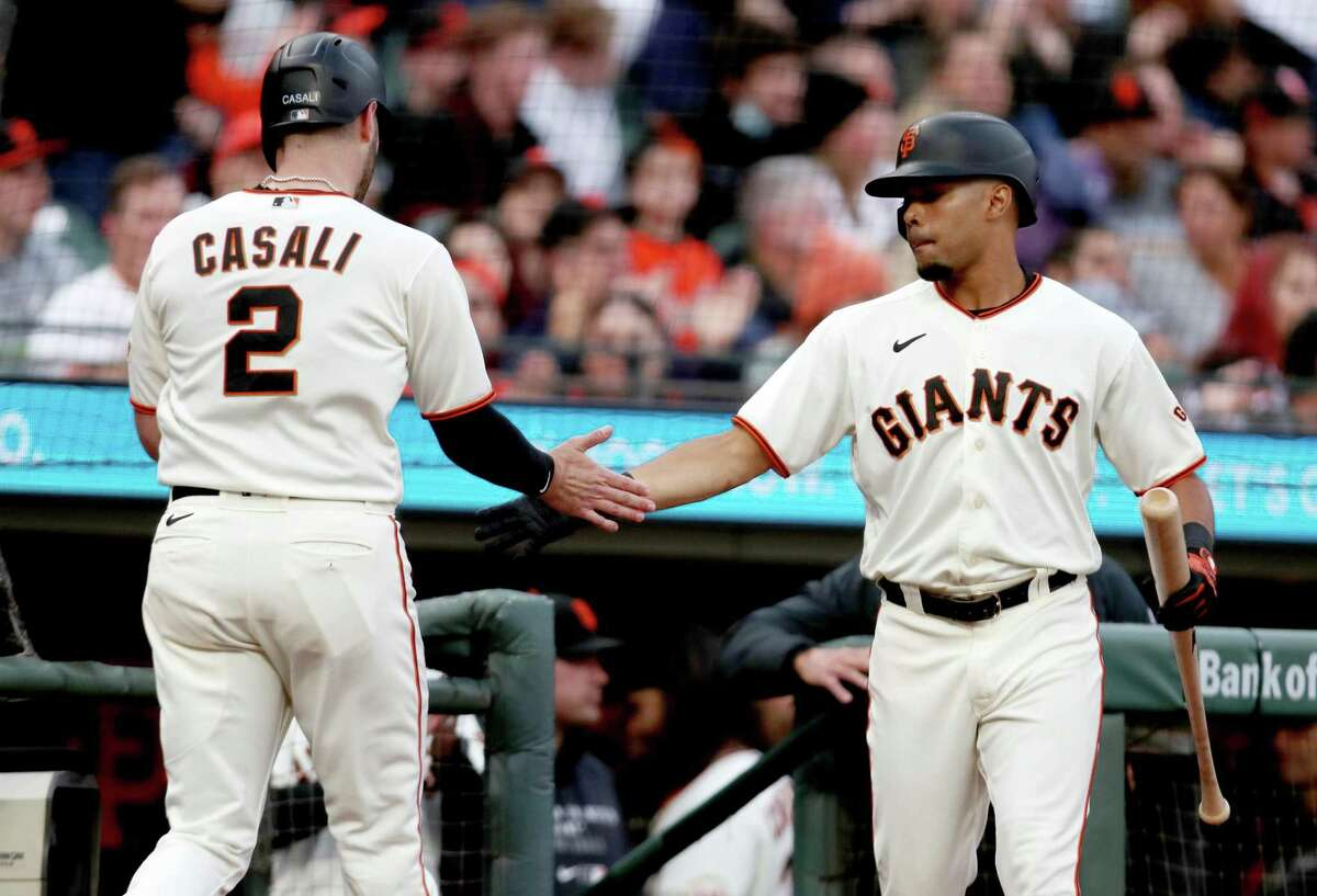 SAN FRANCISCO, CA - AUGUST 12: Curt Casali #2 of the San Francisco Giants is congratulated by teammate LaMonte Wade Jr #31 after scoring on a double by Alex Dickerson against the Colorado Rockies during the second inning at Oracle Park on August 12, 2021 in San Francisco, California. (Photo by Jed Jacobsohn/Getty Images)