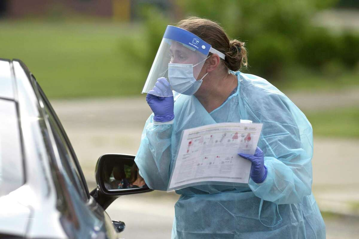 A nurse uses an illustrated pamphlet to explain how to do a self-administered COVID test during the first day of the New Milford Health Department's COVID-19 drive-thru testing site in August.