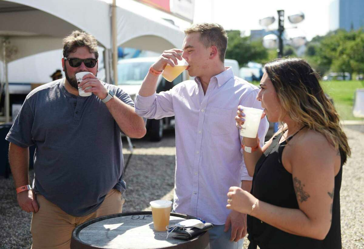 """Craig Sawicki, left, Andrew Zaccagnino, center, and Jillian Flores sip drinks on the opening day of the Hey Stamford! Food Festival at Mill River Park in Stamford, Conn. Thursday, Aug. 12, 2021. The event features a variety of foodie-friendly events including a Blind Rhino happy hour, Slice Slice Baby pizza party, Parm-a-Palooza, and Ice Cream Sunday, in addition to 100 handpicked food and beverage vendors. There will also be live music, including a performance from """"Country Grammar"""" and """"Hot in Herre"""" rapper Nelly on Aug. 14. Presented by Leilo, the event is held Thursday through Sunday this week as well as Thursday through Sunday next week."""