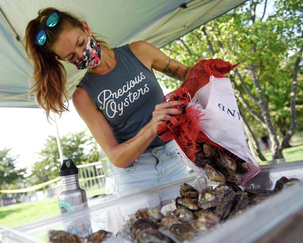 """Precious Oysters owner Rachel Precious arranges her oysters on the opening day of the Hey Stamford! Food Festival at Mill River Park in Stamford, Conn. Thursday, Aug. 12, 2021. The event features a variety of foodie-friendly events including a Blind Rhino happy hour, Slice Slice Baby pizza party, Parm-a-Palooza, and Ice Cream Sunday, in addition to 100 handpicked food and beverage vendors. There will also be live music, including a performance from """"Country Grammar"""" and """"Hot in Herre"""" rapper Nelly on Aug. 14. Presented by Leilo, the event is held Thursday through Sunday this week as well as Thursday through Sunday next week."""